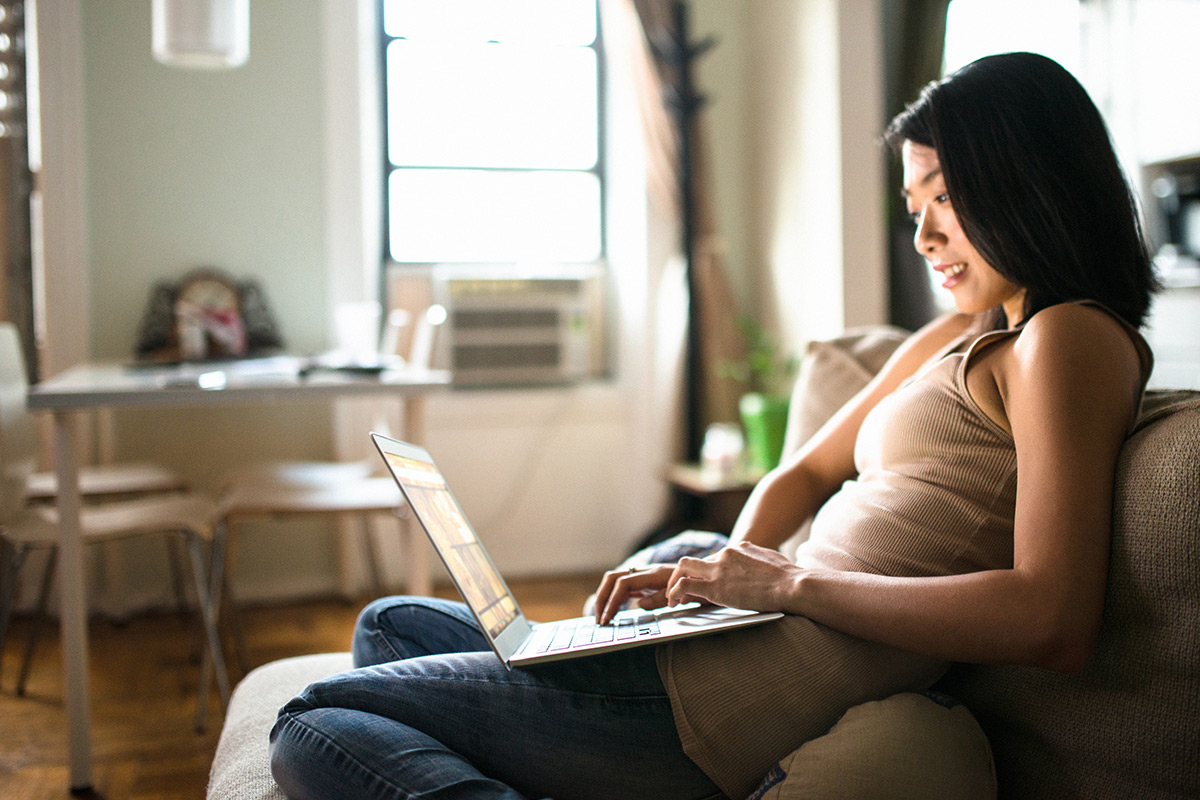 Woman researching renting her home out on laptop