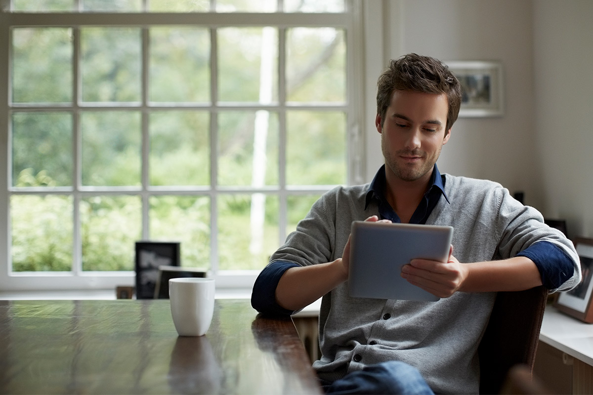 Man researching his home value on a tablet